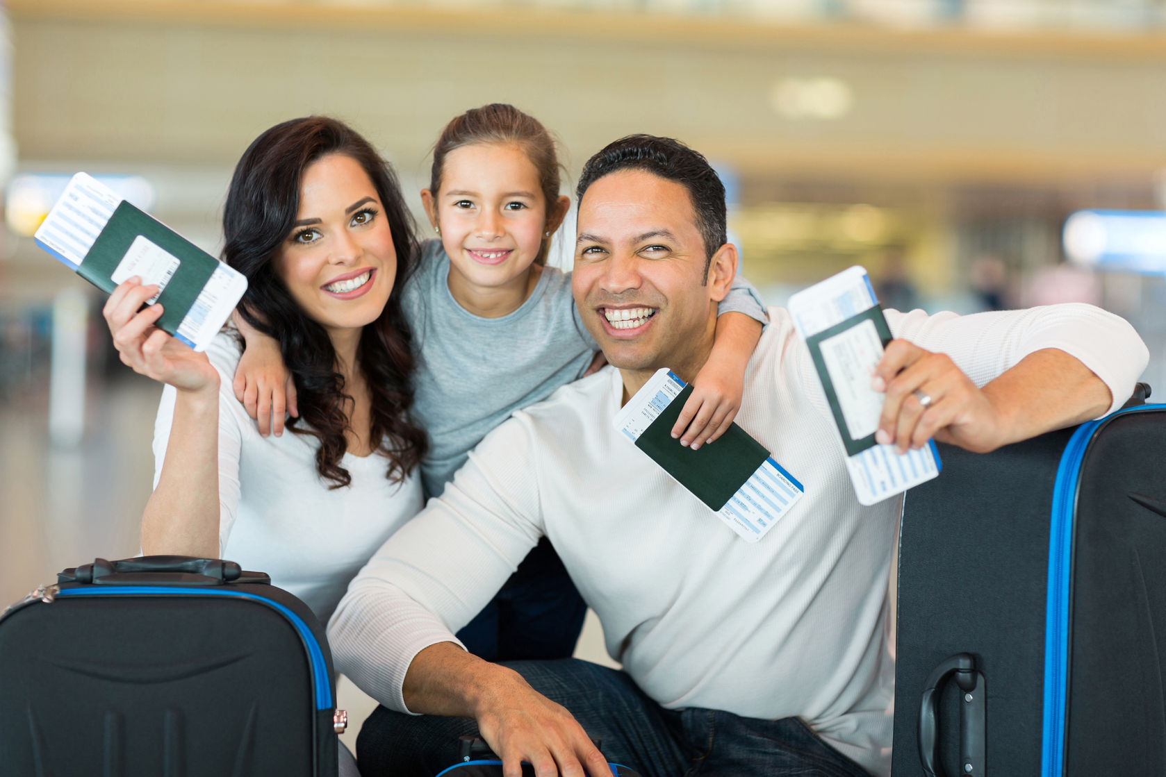 30771955 - happy family holding boarding pass and passport at airport